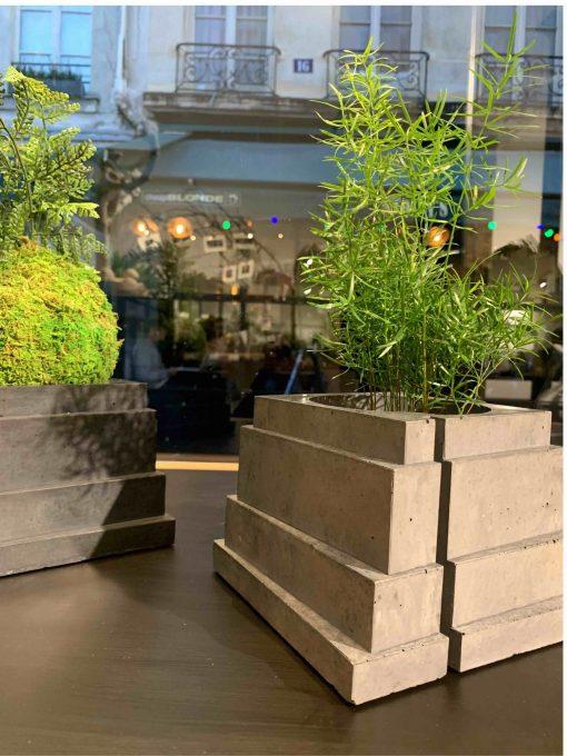 Pot design en béton, modèle Taloul, posé dans une vitrine parisienne