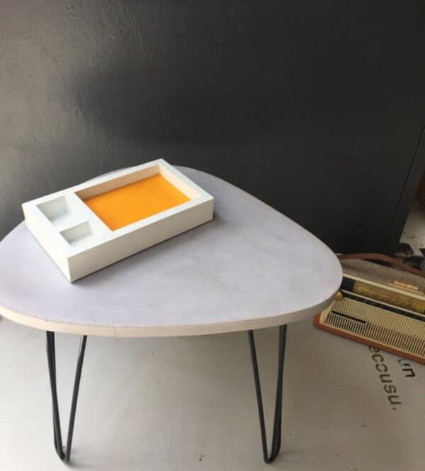 Vide-poches en béton blanc avec cuir couleur moutarde, posée sur une table basse elle aussi en béton
